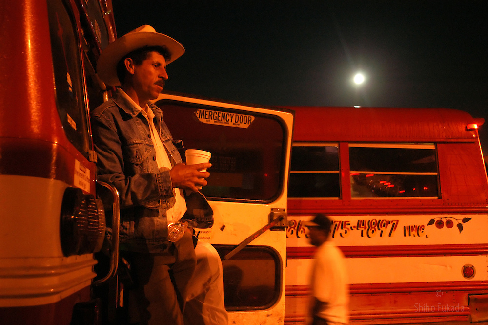Migrant farm workers wait for a bus to take them to the fields in Immokalee, FL, Apr. 16, 2003.