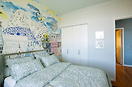 A colorful bedroom with a unique mural located inside a model apartment at the Queens West Building 2 in Long Island City, New York.