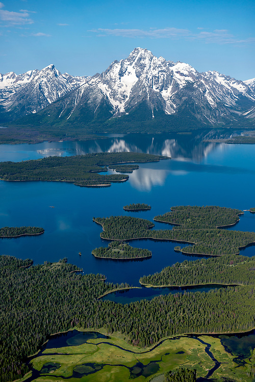 Aerial view of Jackson Lake and the Teton Mountain Range in Teton National Forest on beautiful calm spring morning. Licensing and Open Edition Prints - Vertical