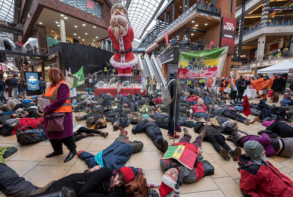 """© Licensed to London News Pictures. 15/12/2018. Bristol, UK. Campaigners stage a """"Die In"""", part of the 'Extinction Rebellion' campaign event """"Bristol Rebellion Day"""" to draw attention to the catastrophic impact of the fast-fashion industry and Christmas on our climate and ecological systems, part of a national day of action in many towns and cities about the threat of climate change. Regional Extinction Rebellion groups are taking part non-violent action to put pressure on local councils to transform policy in line with national demands to act on climate change. Campaigners say Bristol City Council is leading the way, having declared a climate emergency in November. Campaigners gathered inside Cabot Circus on the bottom floor, with songs from the XR Choir and a die in where all activists will lay on the floor. The campaign wants to make ecocide a crime in UK law, saying the threat of climate change threatens the lives of millions of people on the planet. The campaign is organised by Rising Up. Photo credit: Simon Chapman/LNP"""