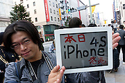 A man holds an ipad with iphone 4S written on it as he stands in the line of people at the Apple store awaiting the official release of the iphone4S in Ginza, Tokyo, Japan. Friday October 14th 2011. The latest version of the popular iphone was released worldwide on October 14th. Japans flagship Apple store in Ginza was opened at 8am for the 800 people that had been waiting to be the first to purchase the new telephone.