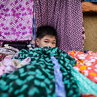 A boy watches a clothing shop the Phú Nhuận vegetable market in Ho Chi Minh City, also known as Saigon, Vietnam.