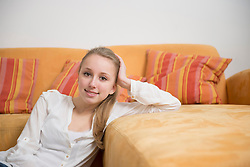 Portrait of teenage girl in living room, smiling