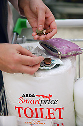 Young woman shopping economically by choosing supermarket brands,