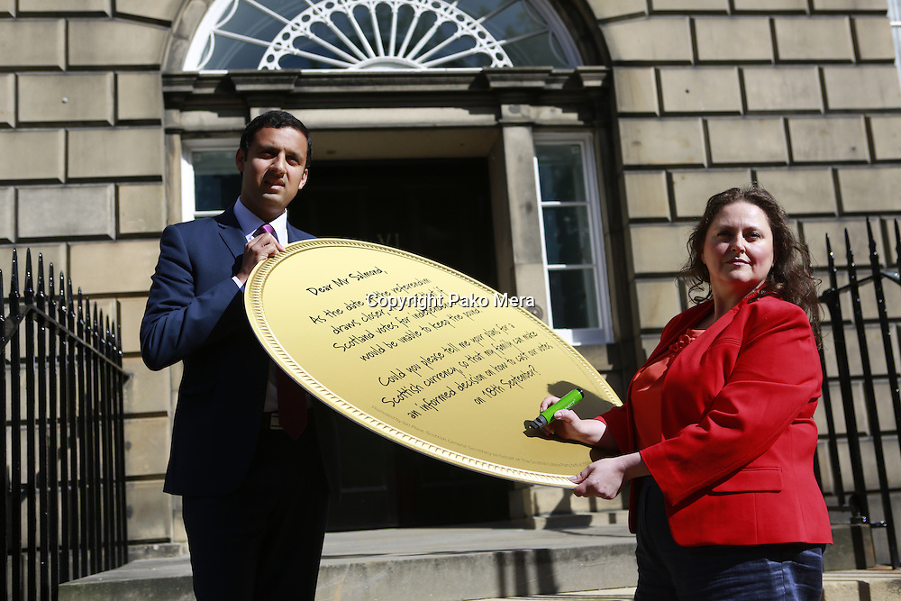 Scottish Labour deputy leader Anas Sarwar and credit union leader worker Alison Dowling deliver a giant pound coin to Bute House. The First Minister's official residence, to highlight uncertainty over what currency an independent Scotland would use.<br /> <br /> Pako Mera. 07/08/2014