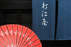 Detail of red parasol and traditional blue curtain at entrance to shop in historic town of Takayama in Japan
