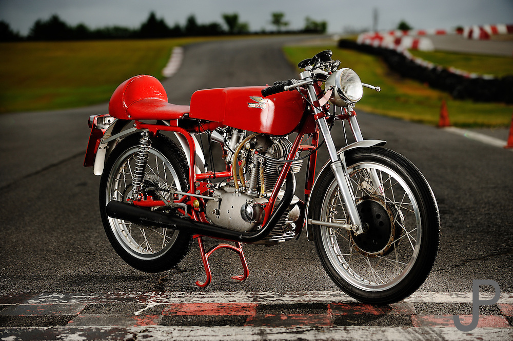 1967 Ducati Mach1/S 250cc motorcycle portrait at Hallett Raceway. This Forumula III Ducati 250 was one of only a dozen made and imported by Berliner for racing purposes only.  The gears are all straight cut and narrowed. The external oil lines to and from the head are unique to the FIII's.  The engine produced 35 HP at 9,000 RPM and ran approximately 135 mph.<br /> This FIII was restored in 1973 using all of the original parts and tires were removed before racing.  This was the last of the springhead racers.  5 star rating.