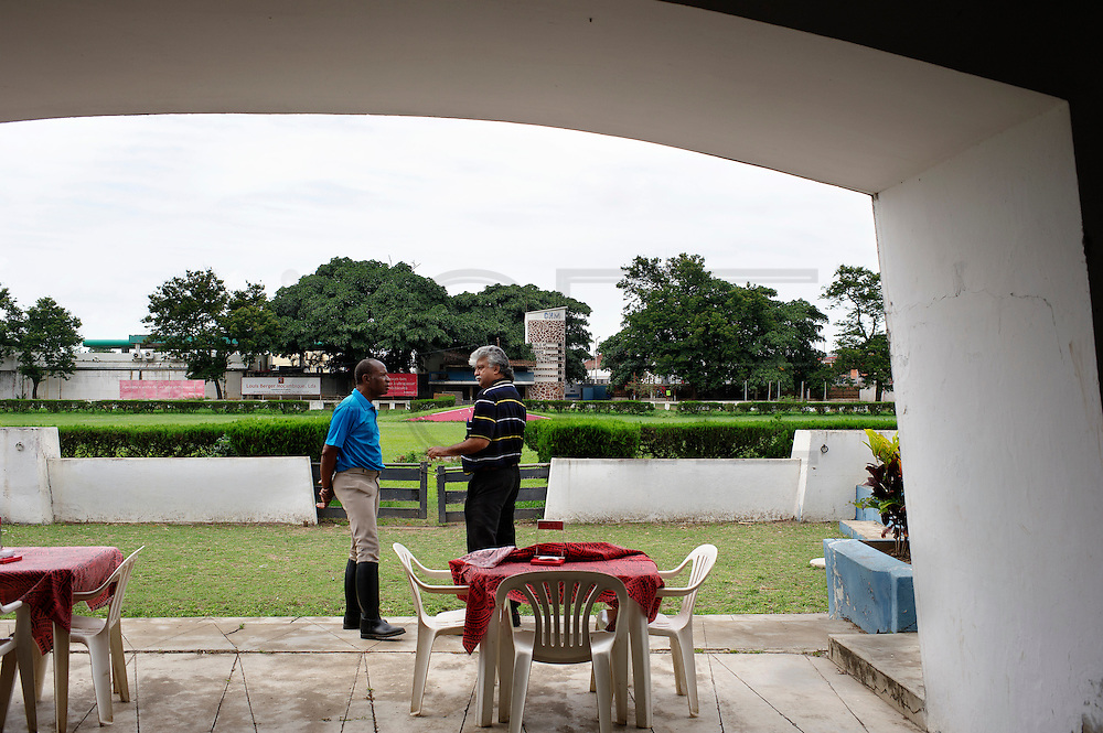 The equestrian centre of Maputo was born in the 1950 during the Portuguese Colonial time. Considered for years one of the most important place of the sub- Saharan Africa for the dressage it resisted to the colonial war and to the Mozambique civil war, his decadence started after the civil war when a poisoned batch of horse food killed most of the animal. Today the centre is trying to resume his old glory living between the past and an uncertain future. 2 members of the Maputo Equestrian Centre speaking outside the members bar.
