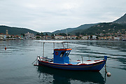 Traditional fishing boat moored in the harbour in Vathy, Ithaca, Greece. Ithaca, Ithaki or Ithaka is a Greek island located in the Ionian Sea to the west of continental Greece. Ithacas main island has an area of 96 square kilometres. It is the second-smallest of seven main Ionian Islands.