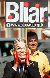 © Licensed to London News Pictures. 06/07/2016. London, UK. A demonstrator dressed as Tony Blair with blood on his hands demonstrates outside QEII centre before Sir John Chilcot makes a statement to the public on the day the report of the Iraq Inquiry is published. The Inquiry was predicated to take approximately one year, but has taken seven. Photo credit : Tom Nicholson/LNP