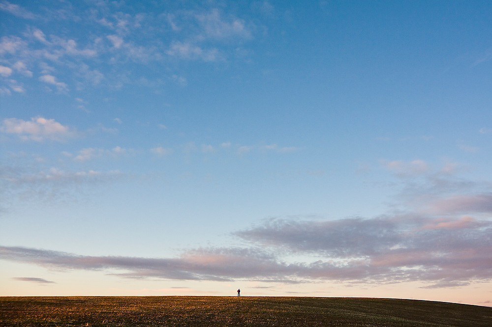 A person stands alone in a field in the Palouse Valley near Spokane, Washington.