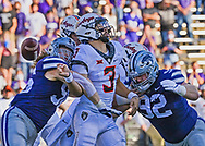 Quarterback Spencer Sanders #3 of the Oklahoma State Cowboys fumbles the ball after getting hit by defensive end Wyatt Hubert #56 of the Kansas State Wildcats and defensive tackle Eli Huggins #92 during the first half at Bill Snyder Family Football Stadium in Manhattan, Kansas.