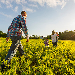 A young family walks in a field in Epping, New Hampshire.