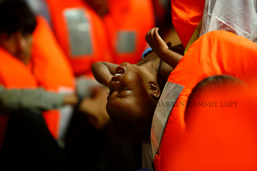 A migrant baby on the Migrant Offshore Aid Station (MOAS) ship MV Phoenix waits to be transferred to the Norwegian ship Siem Pilot off the coast of Libya August 6, 2015.  An estimated 700 migrants on an overloaded wooden boat were rescued 10.5 miles (16 kilometres) off the coast of Libya by the international non-governmental organisations Medecins san Frontiere (MSF) and MOAS without loss of life on Thursday afternoon, according to MSF and MOAS, a day after more than 200 migrants are feared to have drowned in the latest Mediterranean boat tragedy after rescuers saved over 370 people from a capsized boat thought to be carrying 600.<br /> REUTERS/Darrin Zammit Lupi <br /> MALTA OUT. NO COMMERCIAL OR EDITORIAL SALES IN MALTA