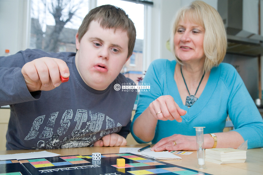 Mother and teenage son with Downs Syndrome playing a board game,