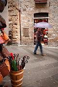 A pedestrian walks with an umbrella in the rain, San Gimignano, Tuscany, Italy.