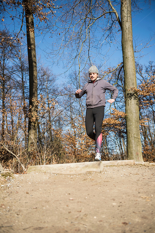 Man doing exercise at obstacle course on fitness trail in forest