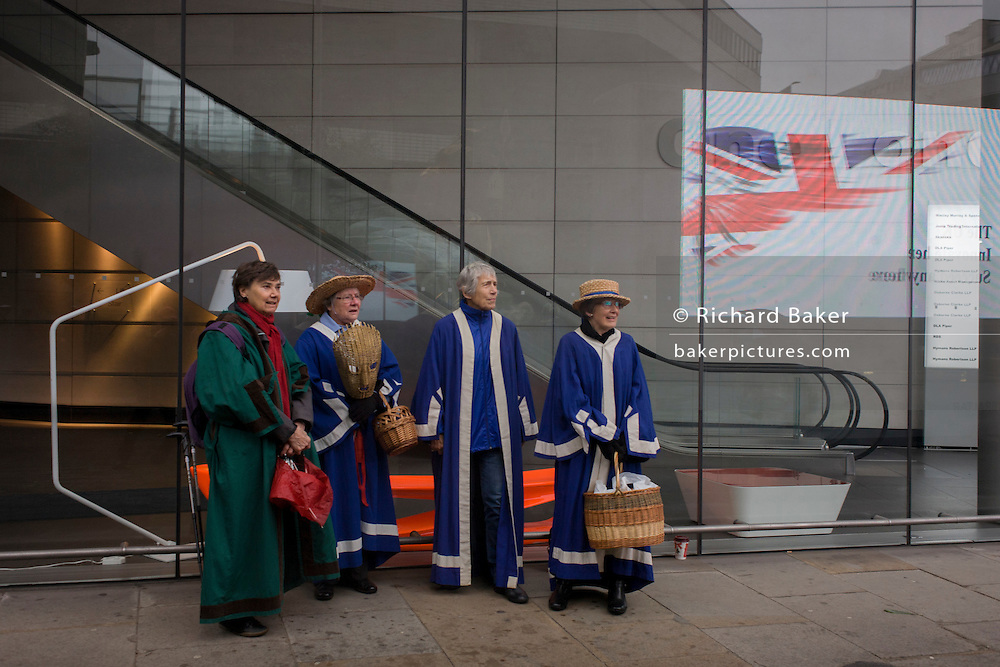 Women from the Guild of Basketmakers before the Lord Mayor's Show in the City of London, the capital's ancient financial district founded by the Romans in the 1st Century. This is the pageant's 800th birthday and the 250 year-old horse-drawn guided State Coach will be pulled through the medieval streets with the newly-elected Mayor along with 7,000 others. This first took place in 1215 making it the oldest and longest civil procession in the world which survived both Bubonic plague and the Blitz.