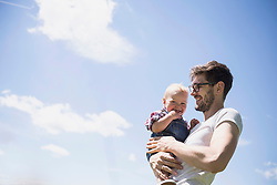 Happy man carrying his son against sky, Bavaria, Germany