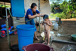 NO WEB/NO APPS - Exclusive. (Text available) A mother washes her child using buckets filled with water stored in common tanks, in 'Palma Real' native community, near Puerto Maldonado, Peru on July 17, 2017. The Amazon rainforest is famous as 'The Lung of the Earth', but also for the presence of numerous native communities, who have always lived isolated and in close contact with nature for generations, used to seek for food and medicines and to build items directly from the environment in which they live. The unstoppable rise of globalization has drastically changed their needs, expectations and consequently their way of life. Located in the Tambopata National Reserve, on the border between Peru and Bolivia, the native Comunidad Palma Real is one of the clearest examples of this change. Living on the banks of the Madre de Dios River since approximately 1976, Palma Real comprises about 300 people part of the nomadic community Ese-Eja, established in the Amazon rainforest of Peru before the Spanish colonization. Photo by Giacomo d'Orlando/ABACAPRESS.COM