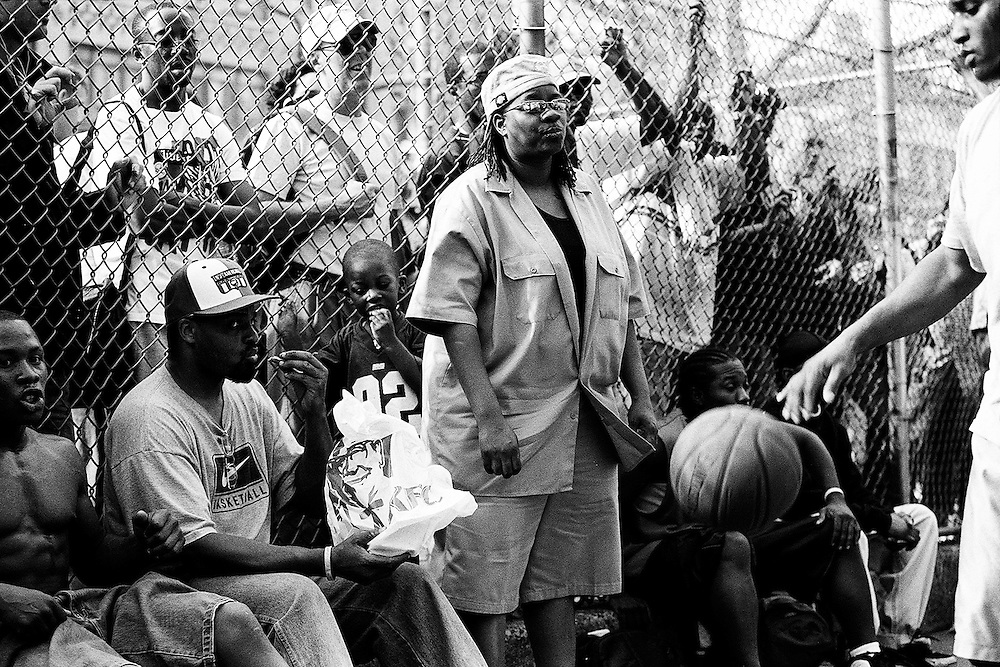 """April 20th 2005. New York, New York. United States..Located in the heart of Greenwich Village, the West 4th Street basketball Court, known as """"The Cage"""", offers no seating but attracts the best players and a lot of spectators as soon as spring is around the corner..Half the size of a regular basketball court, it creates a fast, high level of play. The more people watch, the more intense the games get. « The Cage » is a free show. Amazing actions, insults and fights sometimes, create tensions among and inside the teams. The strongest impose their rules. Charisma is present..""""The Cage"""" is a microcosm. It's a meeting point for the African American street culture of New York. Often originally from Jamaica or other islands of the Caribbean, they hang out, talk, joke, laugh, comment the game, smoke… Whether they play or not, they're here, inside """"The Cage"""". Everybody knows everybody, they all greet each other, they shake hands and hug: """"Yo, whasup man?"""""""