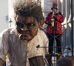 """London, March 13th 2016. The annual St Patrick's Day Parade takes place in the Capital with various groups from the Irish community as well as contingents from other ethnicities taking part in a procession from Green Park to Trafalgar Square.  PICTURED: A giant """"Crom"""" from the Macnas street theatre company in Co Galway dwarfs one of the performers. ©Paul Davey<br /> FOR LICENCING CONTACT: Paul Davey +44 (0) 7966 016 296 paul@pauldaveycreative.co.uk"""
