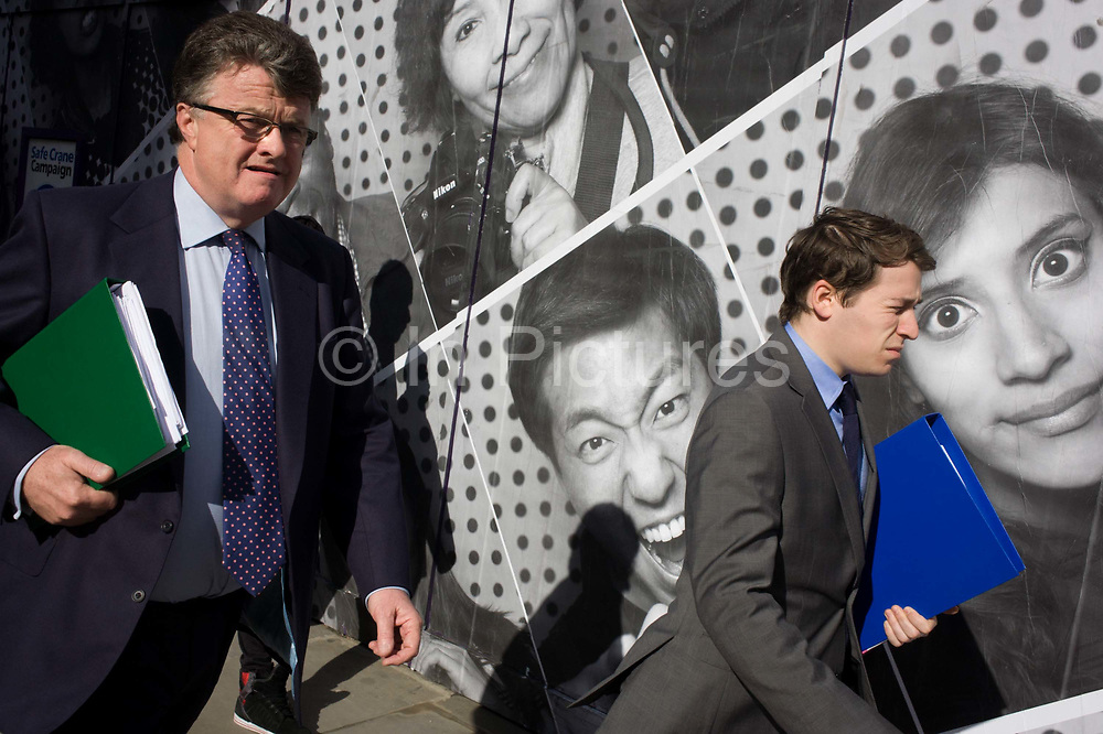 Business associates carrying work folders pass a construction hoarding. The faces and expressions of peoples' appearances feature large in the background as the two men stride past with green and blue ring binders on their way to an appointment - a meeting perhaps, somewhere nearby in the City of London, the capital's financial financial heart and historic centre founded by the Romans in AD43 but now the point of focus for Britain's economy.