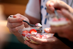 Spectators with strawberries and cream on day four of the Wimbledon Championships at the All England Lawn Tennis and Croquet Club, Wimbledon.