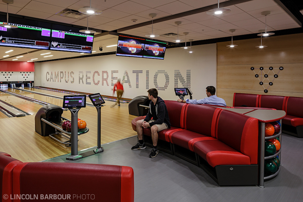 Bowling lanes inside the Liberty Student Center.  One person bowls while two others look on from red couches.