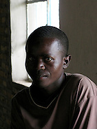 Rwanda- A young Rwandan man sits near the window in the dining hall at the Gary Scheer school.