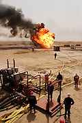 """Firefighters from the Kuwait Oil Company (called KWWK: Kuwait Wild Well Killers) connect hoses to water tanks and a replacement pumps near the second oil well fire they were working on in Iraq's Rumaila Oil field. Later in the day they failed to extinguished this fire with water and then tried to stop the flow of gas and oil with drilling mud using what is called a """"stinger,"""" a tapered pipe on the end of a long steel boom controlled by a bulldozer. Drilling mud, under high pressure, is pumped through the stinger into the well, stopping the flow of oil and gas. This was also unsuccessful. The Rumaila field is one of Iraq's biggest oil fields with five billion barrels in reserve. Many of the wells are 10,000 feet deep and produce huge volumes of oil and gas under tremendous pressure, which makes capping them very difficult and dangerous. Rumaila is also spelled Rumeilah.."""