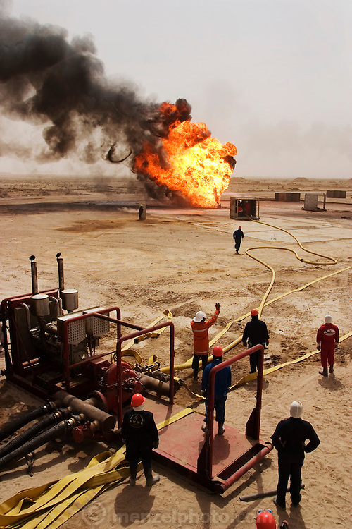 "Firefighters from the Kuwait Oil Company (called KWWK: Kuwait Wild Well Killers) connect hoses to water tanks and a replacement pumps near the second oil well fire they were working on in Iraq's Rumaila Oil field. Later in the day they failed to extinguished this fire with water and then tried to stop the flow of gas and oil with drilling mud using what is called a ""stinger,"" a tapered pipe on the end of a long steel boom controlled by a bulldozer. Drilling mud, under high pressure, is pumped through the stinger into the well, stopping the flow of oil and gas. This was also unsuccessful. The Rumaila field is one of Iraq's biggest oil fields with five billion barrels in reserve. Many of the wells are 10,000 feet deep and produce huge volumes of oil and gas under tremendous pressure, which makes capping them very difficult and dangerous. Rumaila is also spelled Rumeilah.."