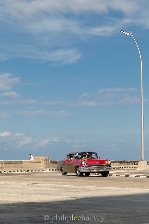 View of red vintage car under blue sky on Malecon road, Havana, Cuba