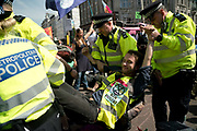 Police arresting a climate protester at Oxford Circus. In an operation that took several hours, Police removed the pink boat named Berta Caceres after the Hondruan nun who was murdered for being an environmental activist, that was the centrepiece of Extinction Rebellions site. It involved people who were locked on being removed. Several roads were blocked across four sites in central London, by the Extinction Rebellion climate change protests, April 2019.