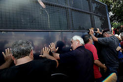 October 3, 2016 - Athens, Greece - Pensioners are trying to overturn police bus that closes the street to the government's headquarters. In Athens, on Monday October 3, 2016. Greek pensioners taking part at a protest march against pension cuts, demanted meeting with Prime minister but were stoped with tear gas by riot police close to Maximos mansion, the government's headquarters. (Credit Image: © Panayiotis Tzamaros/NurPhoto via ZUMA Press)