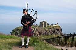 Piper playing pipes in traditional Scottish kilt at Dunnottar Castle in Aberdeenshire Scotland UK