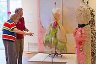 Roslyn, New York, U.S. - April 12, 2014 - During International Slow Art Day, visitors view a Robe de Style dress and an Evening Coat by Callot Soeurs, and an Evening Ensemble by Mainhocker, at the Garden Party exhibit at the Nassau County Museum of Art on Long Island. During this annual worldwide event, those participating (not known if those shown are participants) went to local museums and viewed a small number of works of art, each for at least 10 minutes, and then discussed them afterward.