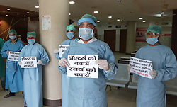 April 16, 2020, Prayagraj, Uttar Pradesh, India: Prayagraj: Doctors hold placard as they protest against attack on doctors team at various places during Coronavirus inspection during a nationwide lockdown imposed as a preventive measure against the spread of the COVID-19 coronavirus in Allahabad (Credit Image: © Prabhat Kumar Verma/ZUMA Wire)