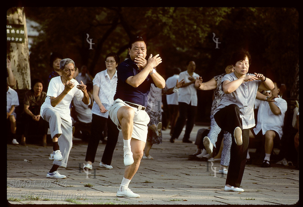 Teacher dressed in shorts does t'ai chi as students follow from behind in Jin An Park; Shanghai. China