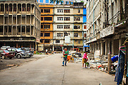 """12 DECEMBER 2012 - BANGKOK, THAILAND:  A family of demolition workers walk through the buildings they are tearing down """"Washington Square"""" a notorious entertainment district off Sukhumvit Soi 22 in Bangkok. Demolition workers on many projects in Thailand live on their job site tearing down the building and recycling what can recycled as they do so until the site is no longer inhabitable. They sleep on the floors in the buildings or sometimes in tents, cooking on gas or charcoal stoves working from morning till dark. Sometimes families live and work together, other times just men. Washington Square was one of Bangkok's oldest red light districts. It was closed early 2012 and is being torn down to make way for redevelopment.    PHOTO BY JACK KURTZ"""