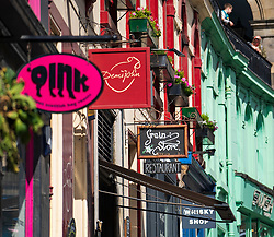 Shop and restaurant signs on historic Victoria Street in Edinburgh Old town, Scotland, UK