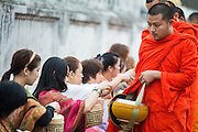 """11 MARCH 2013 - LUANG PRABANG, LAOS:  Women give food to Buddhist monks during the tak bat in Luang Prabang. The """"Tak Bat"""" is a daily ritual in most of Laos (and other Theravada Buddhist countries like Thailand and Cambodia). Monks leave their temples at dawn and walk silently through the streets and people put rice and other foodstuffs into their alms bowls. Luang Prabang, in northern Laos, is particularly well known for the morning """"tak bat"""" because of the large number temples and monks in the city. Most mornings hundreds of monks go out to collect alms from people.   PHOTO BY JACK KURTZ"""