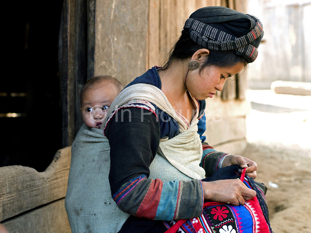 A Mouchi ethnic minority woman wearing traditional clothing and carrying her baby son on her back sews traditional clothing outside her home in Ban Nam Sa, Phongsaly province, Lao PDR. One of the most ethnically diverse countries in Southeast Asia, Laos has 49 officially recognised ethnic groups although there are many more self-identified and sub groups. These groups are distinguished by their own customs, beliefs and rituals.  Details down to the embroidery on a shirt, the colour of the trim and the type of skirt all help signify the wearer's ethnic and clan affiliations.