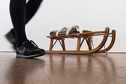 "© Licensed to London News Pictures. 17/04/2018. LONDON, UK. A staff member walks by ""Schlitten (Sled)"", 1969, wooden sled with felt, cloth, straps, torch, wax and cord, at the preview of ""Joseph Beuys: Utopia at the Stag Monuments"", at the Galerie Thaddaeus Ropac in Dover Street.  The retrospective is the most important UK exhibition of Beuys' work in over a decade, presenting major sculptures and rarely seen works from 1947 to 1985, and runs from 18 April to 16 June.  Photo credit: Stephen Chung/LNP"
