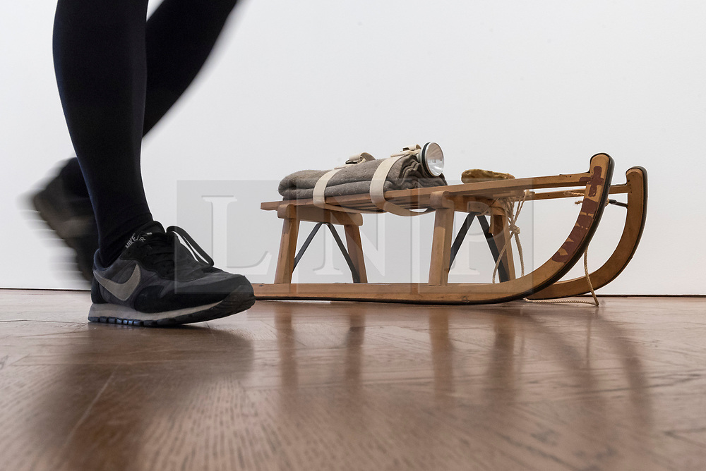 """© Licensed to London News Pictures. 17/04/2018. LONDON, UK. A staff member walks by """"Schlitten (Sled)"""", 1969, wooden sled with felt, cloth, straps, torch, wax and cord, at the preview of """"Joseph Beuys: Utopia at the Stag Monuments"""", at the Galerie Thaddaeus Ropac in Dover Street.  The retrospective is the most important UK exhibition of Beuys' work in over a decade, presenting major sculptures and rarely seen works from 1947 to 1985, and runs from 18 April to 16 June.  Photo credit: Stephen Chung/LNP"""