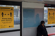 The day after UK Prime Minister Boris Johnson addressed the nation with his roadmap for the coming weeks and months during the Coronavirus pandemic lockdown, a lady wearing a surgical face mask sits in a Camberwell bus stop in between two posters encouraging social distancing on the capitals transport network, on 11th May 2020, in London, England.