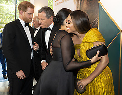The Duke of Sussex speaks with Disney CEO Robert Iger as the Duchess of Sussex embraces Beyonce at the European Premiere of Disney's The Lion King at the Odeon Leicester Square, London.