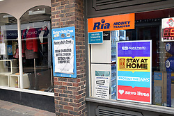 Eastern Daily Press headline next to NHS digital poster in newsagent window during Coronavirus lockdown, Norwich UK April 2020