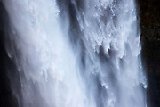 A close-up view captures the rough texture of water surging over Snoqualmie Falls in Snoqualmie, Washington.