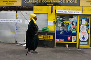A local lady passes-by the looted Clarence Convenience Store belonging to Sri Lankan-born Sivaharan (Siva) Kandiah. During the riot in London on Monday 8th August, local youths and older residents of nearby estates ransacked the business and either removed Siva's stock or left the rest to spoil on the unrefrigerated floor. In alcohol and cigarettes alone, he lost £50,000 in stock but during the campaign top help him recover, more than £16,000 was raised by his customers and friends.